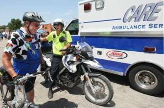 Mobile paramedic Ben Caskey, 29, gives advice to rider Tom Pockrandt, who said he was waiting for the sag wagon to come by. (Mary Chind/The Register)