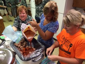 Our Savior United Methodist Church members Rita Cue, Holly Witham and Kim Fryman load up another tub of hamballs.